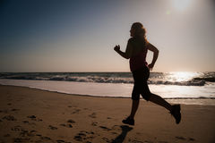 Woman running on the beach. A woman running on the beach at sunrise Royalty Free Stock Image