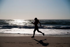 Woman running on the beach. A woman running on the beach in silhouette at sunrise Royalty Free Stock Photography
