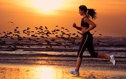 Woman running on the beach. And sunset