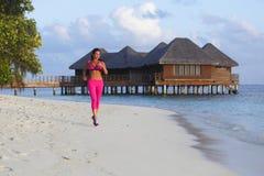 Woman running on beach Stock Photo
