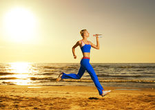 Woman running on a beach. Beautiful young woman running on a beach at sunset (real shot, background is not photoshopped in Royalty Free Stock Images