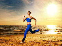 Woman running on a beach. Beautiful young woman running on a beach at sunset Royalty Free Stock Photography