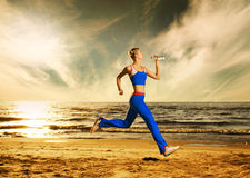 Woman running on a beach Stock Image