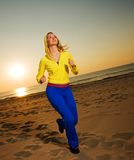 Woman running on a beach. Beautiful young woman running on a beach at sunset Stock Photo