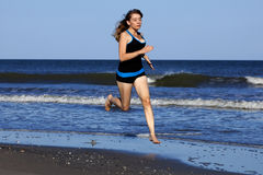 Woman running on the beach barefooted Stock Images