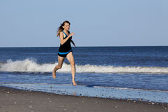 Woman running on the beach barefooted.  Royalty Free Stock Image