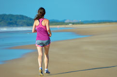 Woman running on beach, beautiful girl runner jogging Stock Image