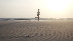 Woman running at the beach stock video footage