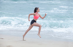 Woman running on the beach at cloudy morning, side view Royalty Free Stock Photography