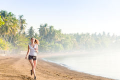 Woman running on the beach Stock Image