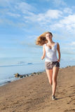 Woman running on the beach Stock Images
