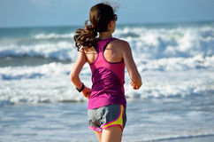 Woman running on beach, girl runner jogging outdoors. Woman running on beach, beautiful girl runner jogging outdoors, training for marathon, exercising and Royalty Free Stock Image