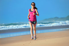 Woman running on beach, girl runner jogging outdoors Stock Image