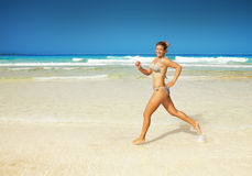 Woman running on the beach. Happy beautiful woman running on the beach Stock Image