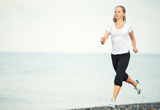 Woman running on the beach. Morning jog. young woman running on the beach on the coast of the Sea Royalty Free Stock Photo