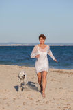 Woman running on beach with pet dog Royalty Free Stock Photo