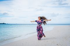 Woman running on beach with transparent water of ocean in Maldives Stock Photos