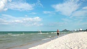 Woman running on the beach stock footage