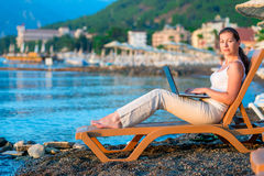 Woman running on the beach on a sun lounger Royalty Free Stock Photography