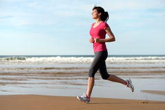 Fitness woman running on beach. Woman running on the beach at sunset. Beautiful fitness caucasian girl exercising outdoors on sea background. Copy space Stock Images