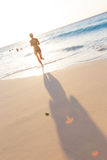 Woman running on the beach in sunset. Stock Image