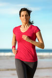 Woman running on beach at sunset. Woman running on beach in summer day at sunset.  Happy fitness girl exercising on sea background. Beautiful caucasian brunette Stock Photography