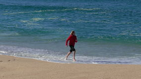 Woman Running on Beach with Waves. In the Background stock video