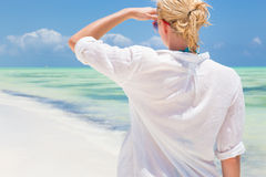 Woman running on the beach in white shirt. Royalty Free Stock Image
