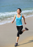 Woman running at beach. Young fit asian woman running at beach Royalty Free Stock Image