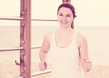 Woman running on beach. Young fit woman running on beach in sunny morning Stock Photography