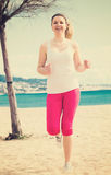 Woman running on beach. Young fit woman running on beach in sunny morning Stock Photo