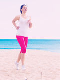 Woman running on beach. Young sporty woman running on beach by ocean in morning Stock Photos
