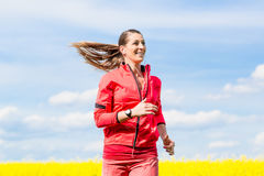 Woman running for better fitness in spring Royalty Free Stock Images