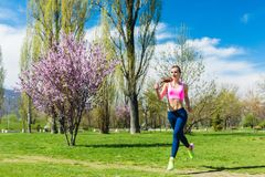 Woman running for better fitness though a park in spring stock image