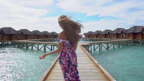 Woman running on bridge on beach with transparent water of ocean in Maldives. Woman running on bridge on beach with pure transparent water of ocean in Maldives stock video footage