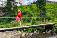 Woman running on bridge in mountains on summer day Royalty Free Stock Photos