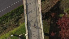 Woman running on a bridge over a freeway from above stock video