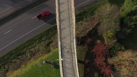 Woman running on a bridge over a freeway from above stock footage
