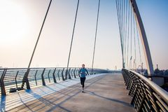 Woman running on the bridge on a sunny day royalty free stock photography