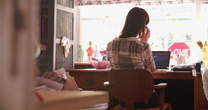 Woman Running Business From Home Office Answering Phone. Rear view of woman working in home office answering phone call on mobile.Shot on Sony FS700 at frame stock video