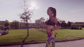 Woman running in a city park stock video
