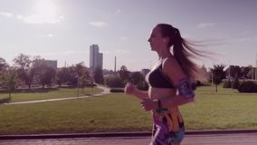 Woman running in a city park stock footage