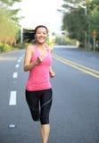 Woman running at city road Royalty Free Stock Photos