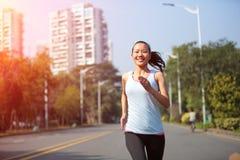 Woman running at city street Royalty Free Stock Image