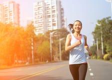 Woman running at city street Stock Photo