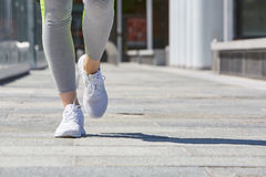 Woman running in the city with tracksuit, sunlight Stock Image
