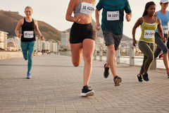 Woman with running club group stretching after a run Stock Photo