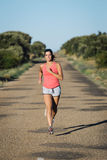 Woman running on country asphalt road Stock Photo