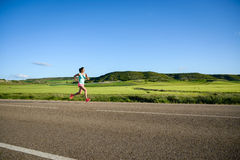 Woman running on countryside road Stock Photography