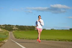 Woman running on countryside road Stock Images